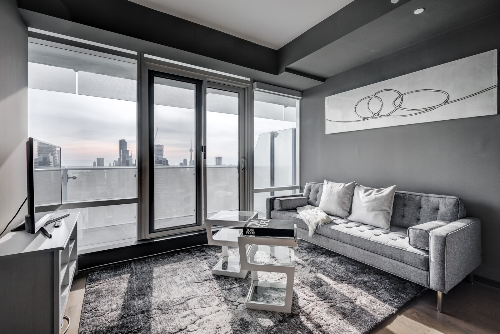 Gray-coloured living room walls, ceiling and carpet with view of CN Tower windows of 1 Bloor St E Unit 4305.