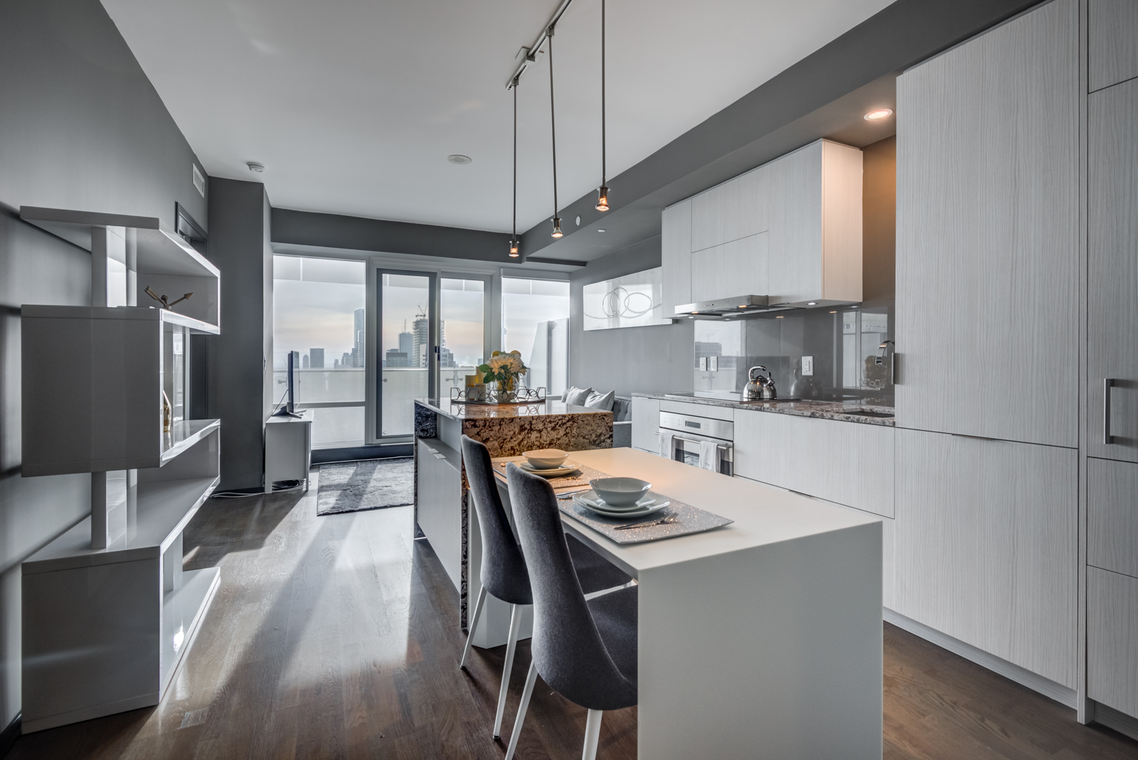1 Bloor St E Unit 4305 white breakfast bar with two gray chairs and pendant lights.