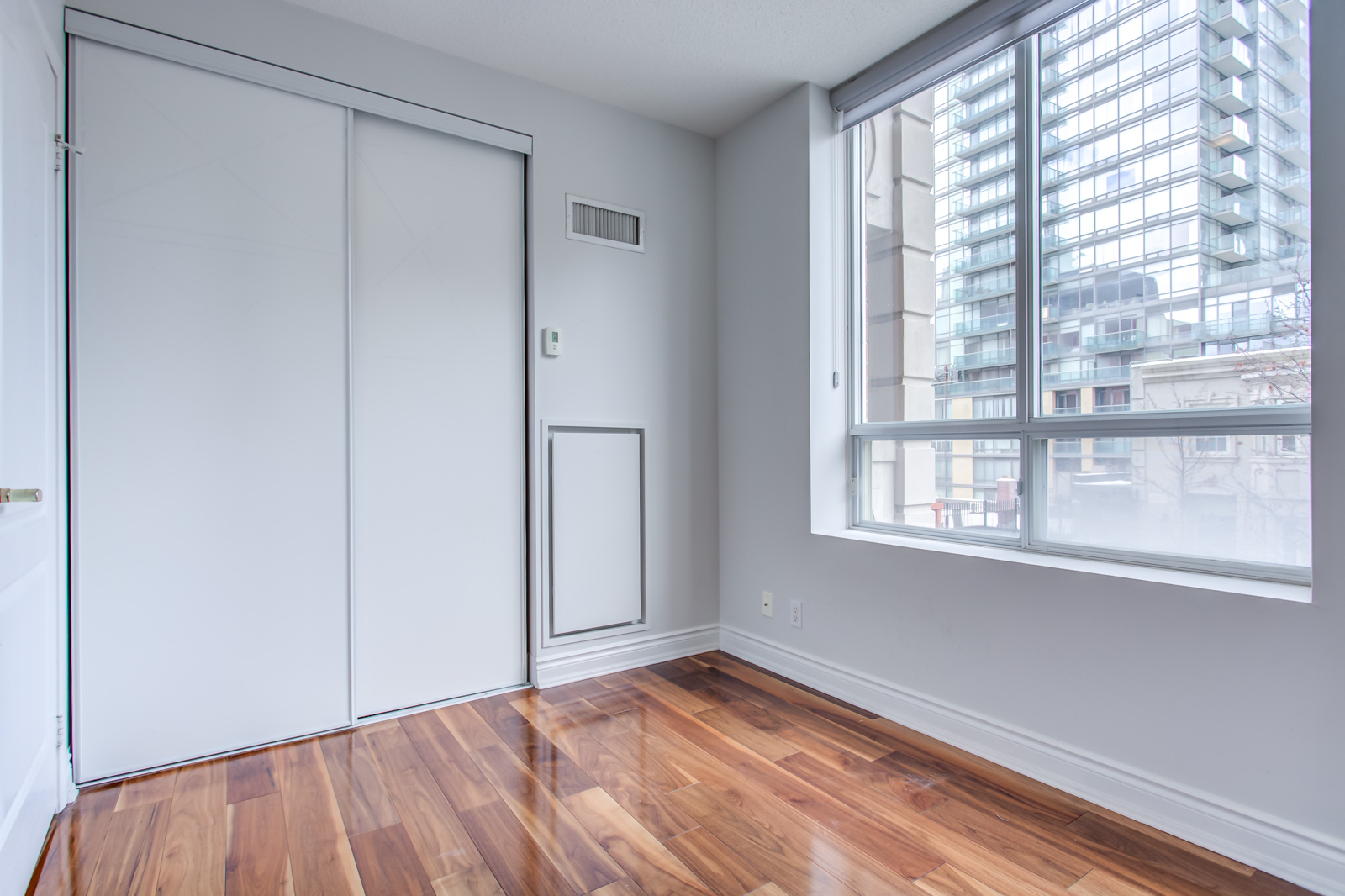 Small empty bedroom with shiny brown hardwood floors and large window showing building.