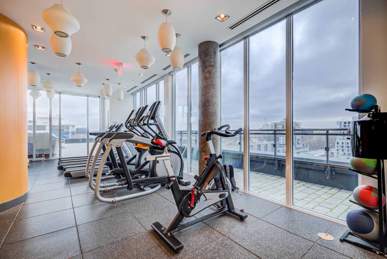 Several stationary bikes facing windows in Fabrik Condos PH 101.