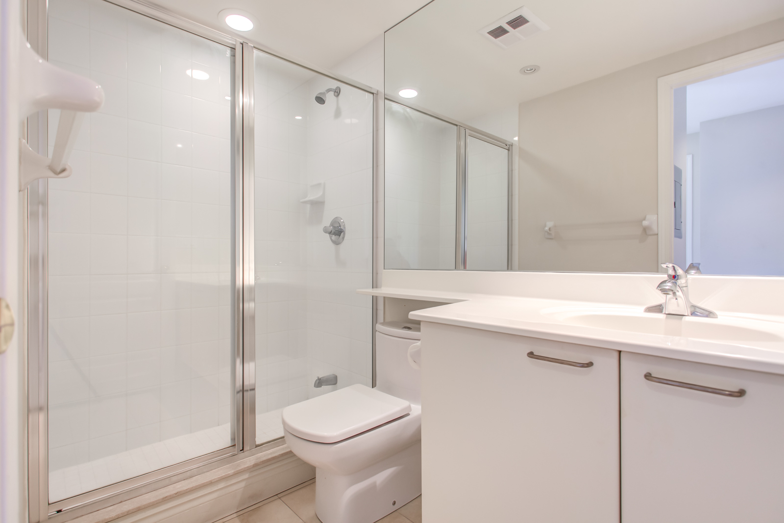 Washroom of 20 Collier St Unit 408 with walk-in shower, white sink and cabinet, and huge mirror.