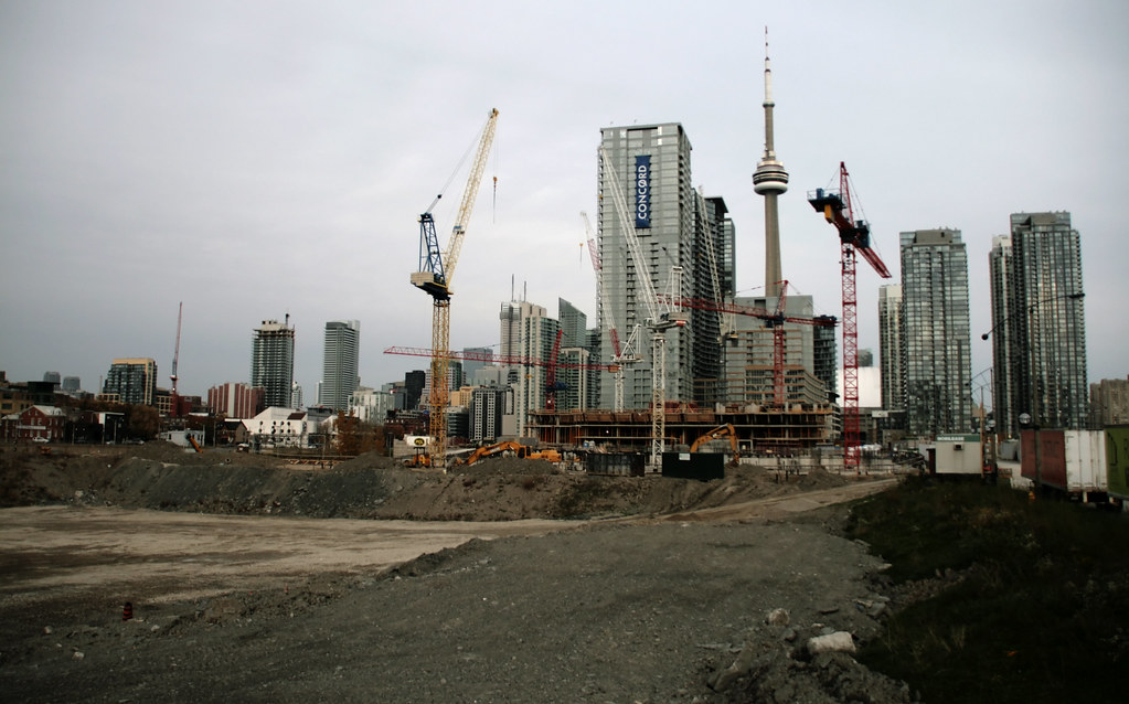 Construction cranes in the Fashion District with CN Tower in background.