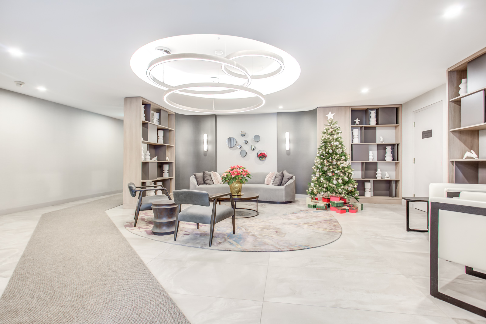 Twenty Collier lobby with Christmas tree, red flowers in vase and shelves full of ornaments.