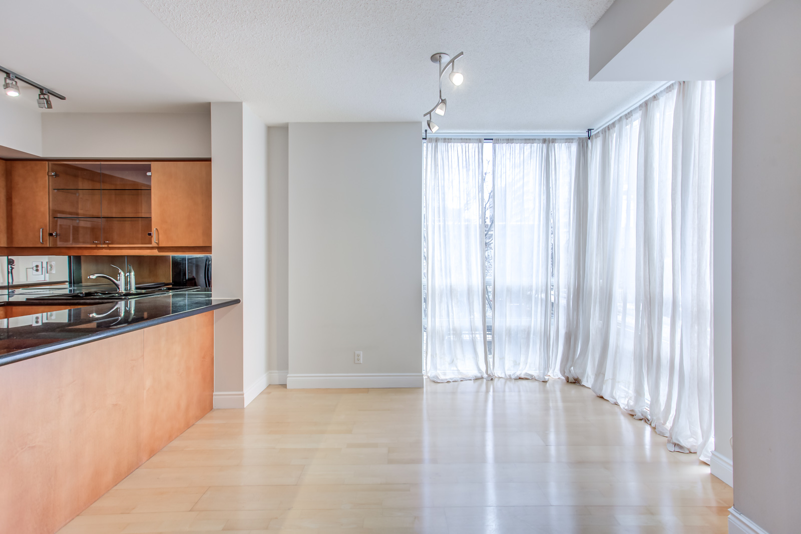 View of 20 Collier St Unit 408 kitchen on left and dining room on right with white curtains.