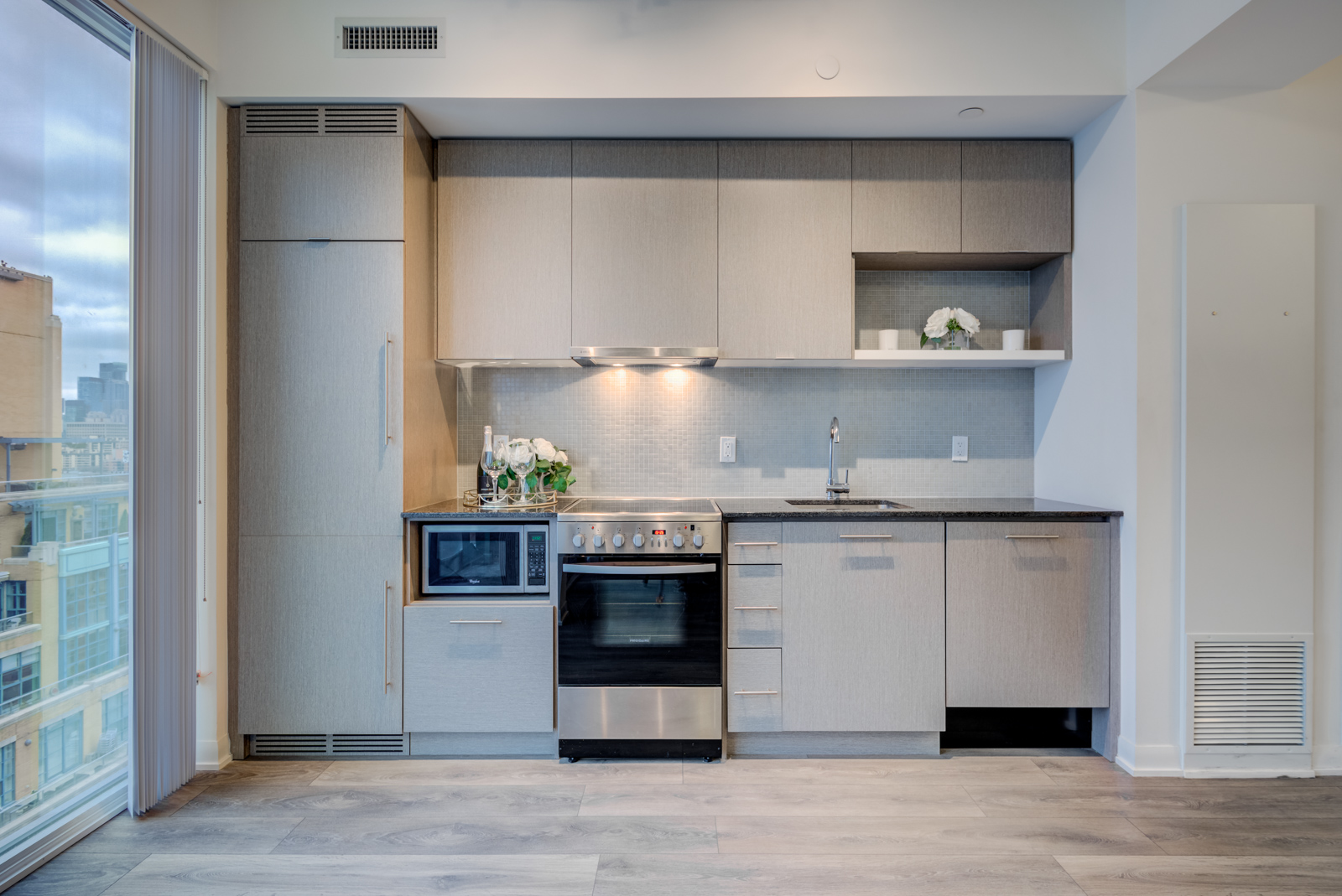 Linear kitchen with stainless-steel stove, cooktop and microwave.