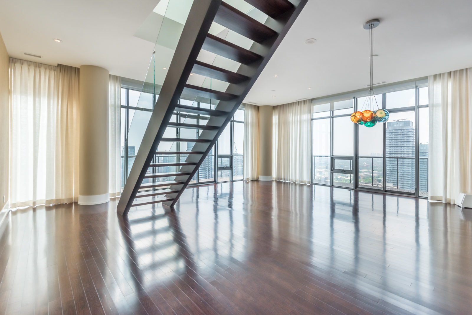 Empty penthouse with shiny floors and staircase with glass panels; most expensive property at 33 Charles St E Casa Condos.