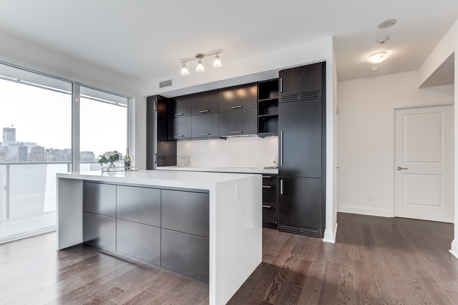 Linear kitchen with dark wood cabinets and silver appliances at 65 St Mary St at U Condominiums.