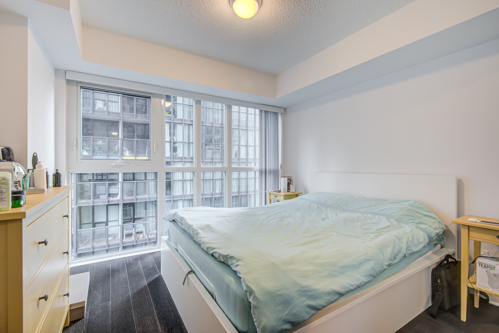 28 Ted Rogers Unit 1702 master bedroom with large bed, floor-to-ceiling windows and gray walls.