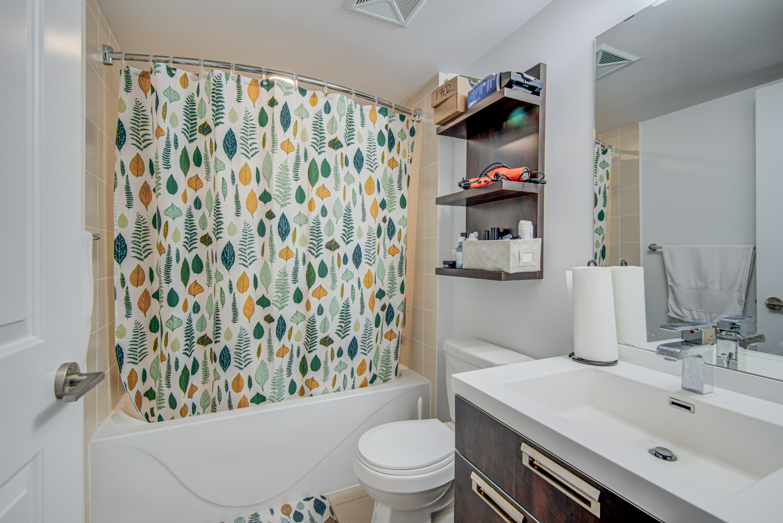 Bathroom with floral shower curtain, white tub and sink, large mirror and shelves with hairdryer and toiletries.