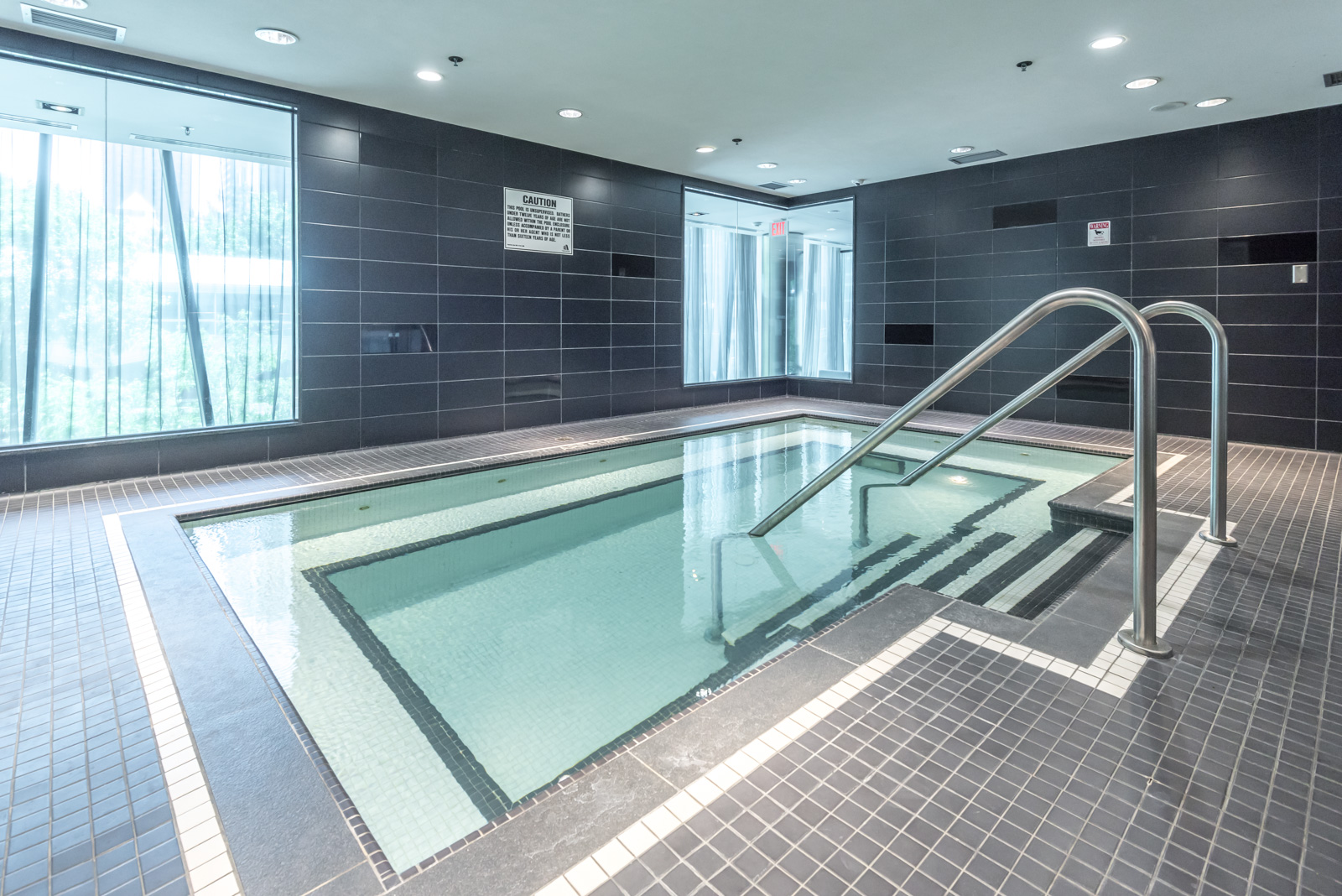 Indoor swimming pool with light green water at The Couture condos.