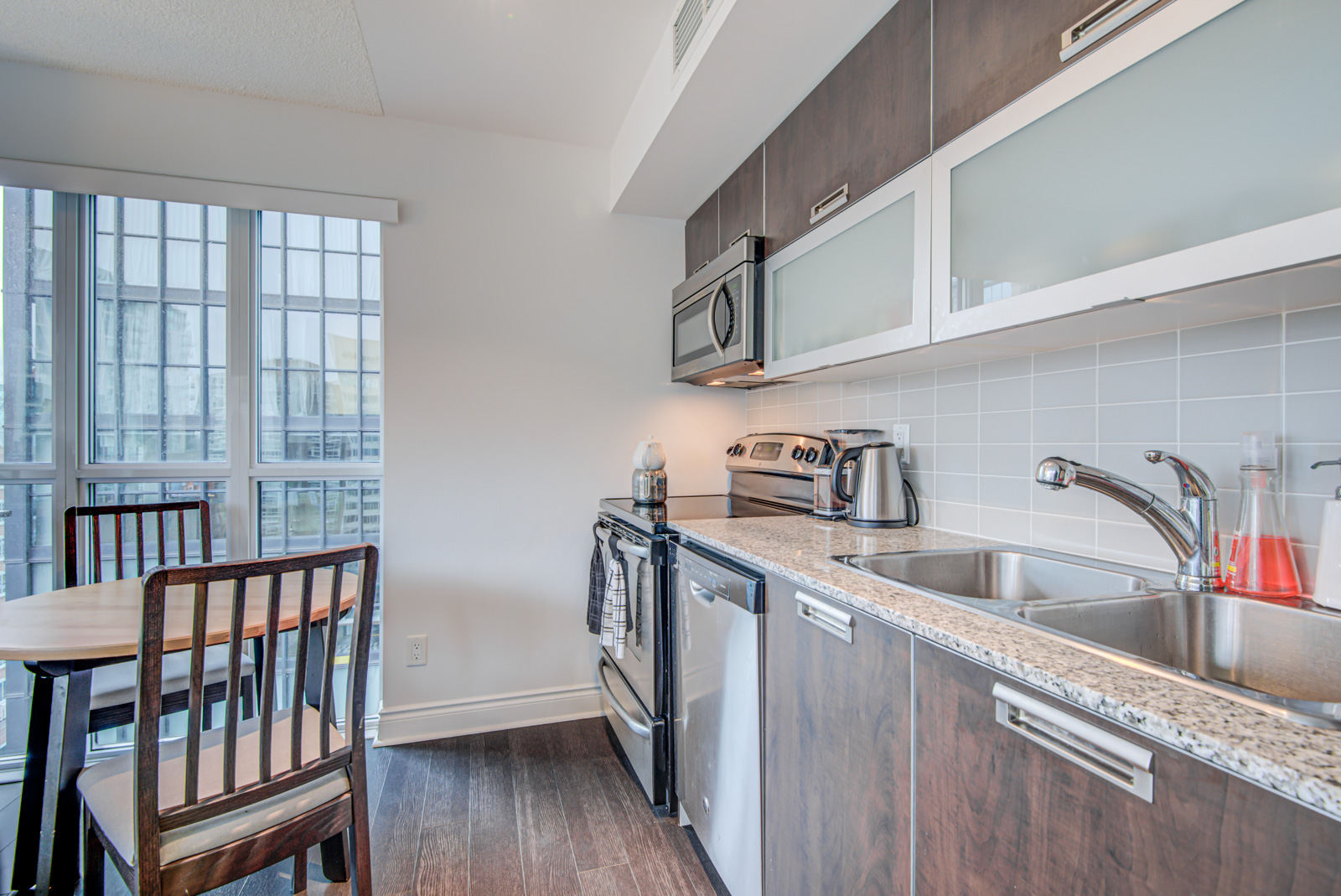 Linear kitchen of 28 Ted Rogers Unit 1702 with built-in appliances, wooden cupboards and frosted-glass shelves.