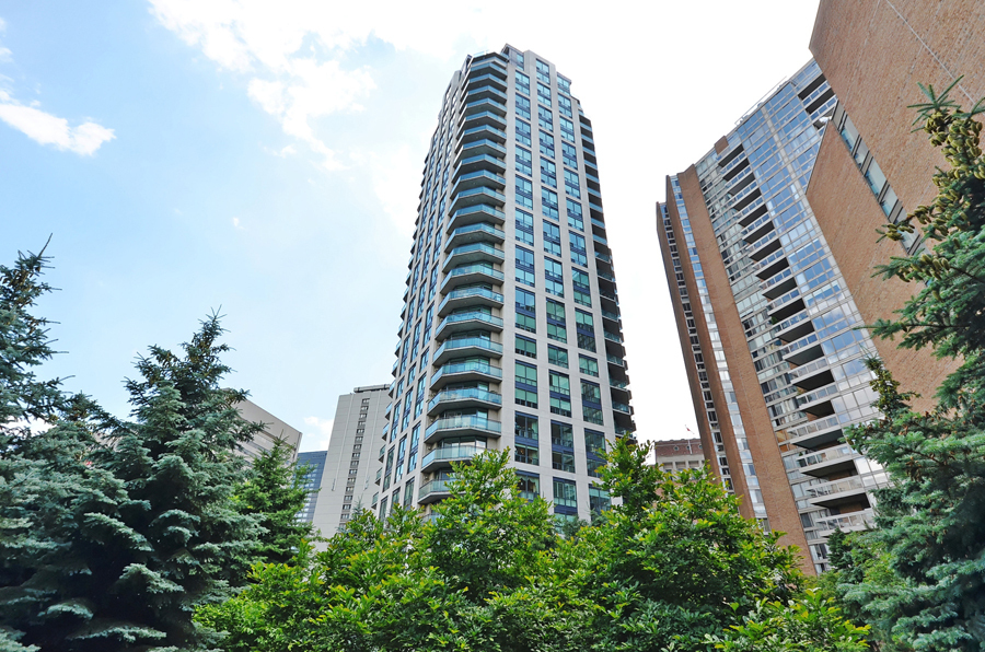 View of Bellagio on Bloor Condos from park; the 28-story building is very symmetrical and uses a lot of blue glass.