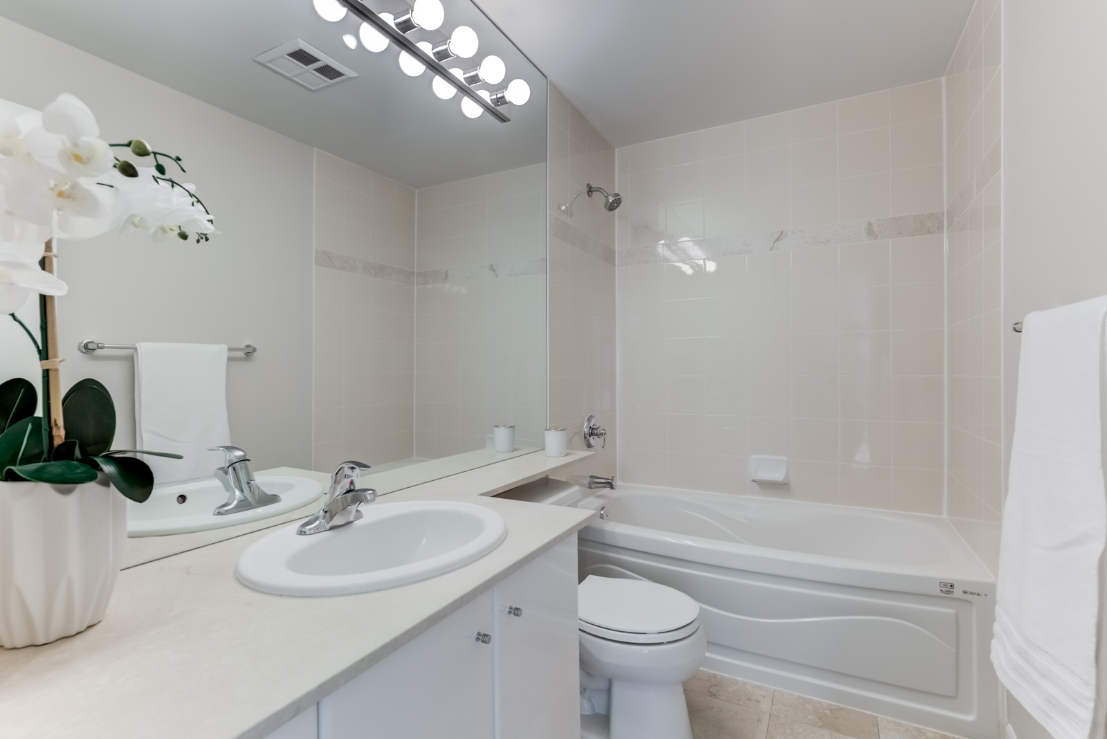 300 Bloor St E Unit 1809 ensuite bath with white counters, cabinets, beige tiles, white tub and chrome fixtures.