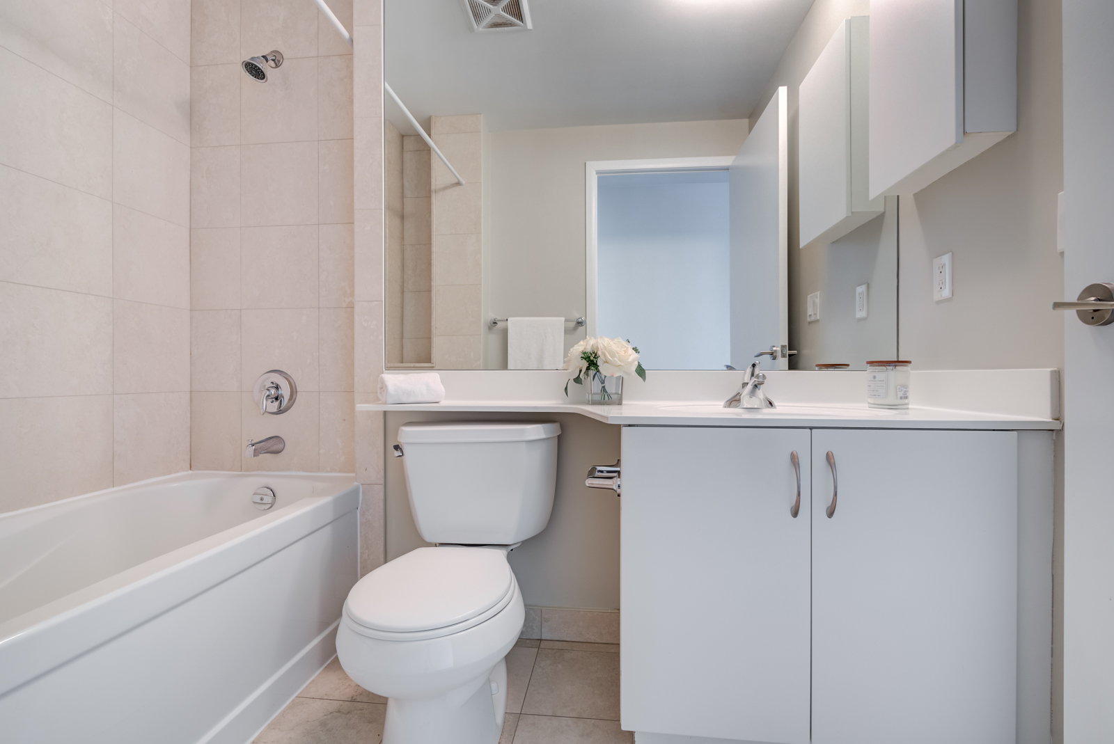 215 Fort York Blvd ensuite bath with white toilet, tub, sink, cabinets and huge mirror.