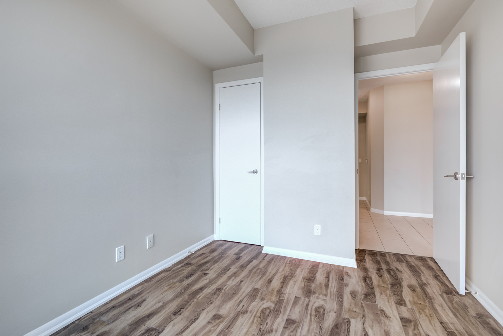Empty bedroom with dark laminate floors, gray walls and white closet door.