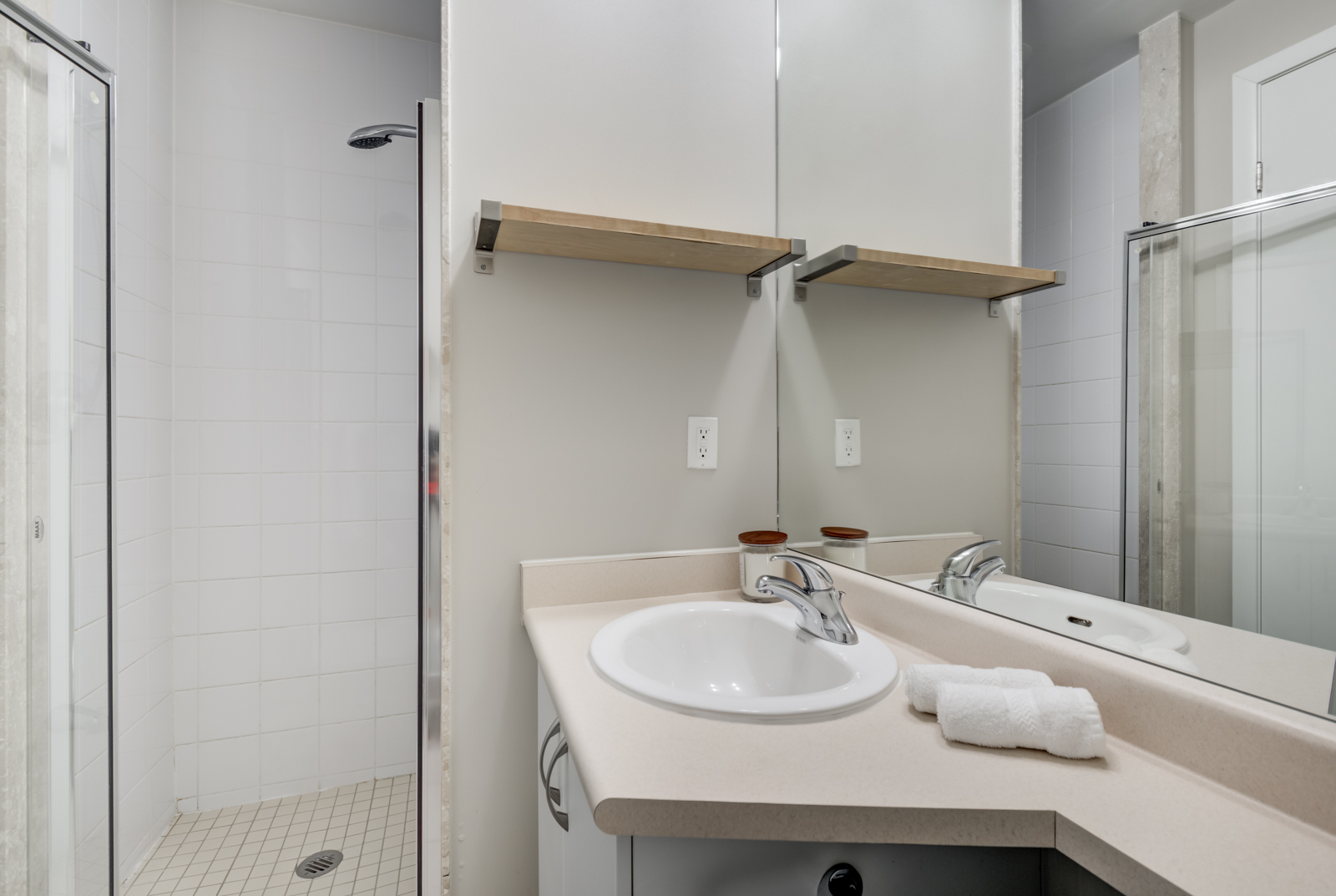Small bathroom with oval sink, silver faucet, wooden shelf, walk-in shower and large mirror.
