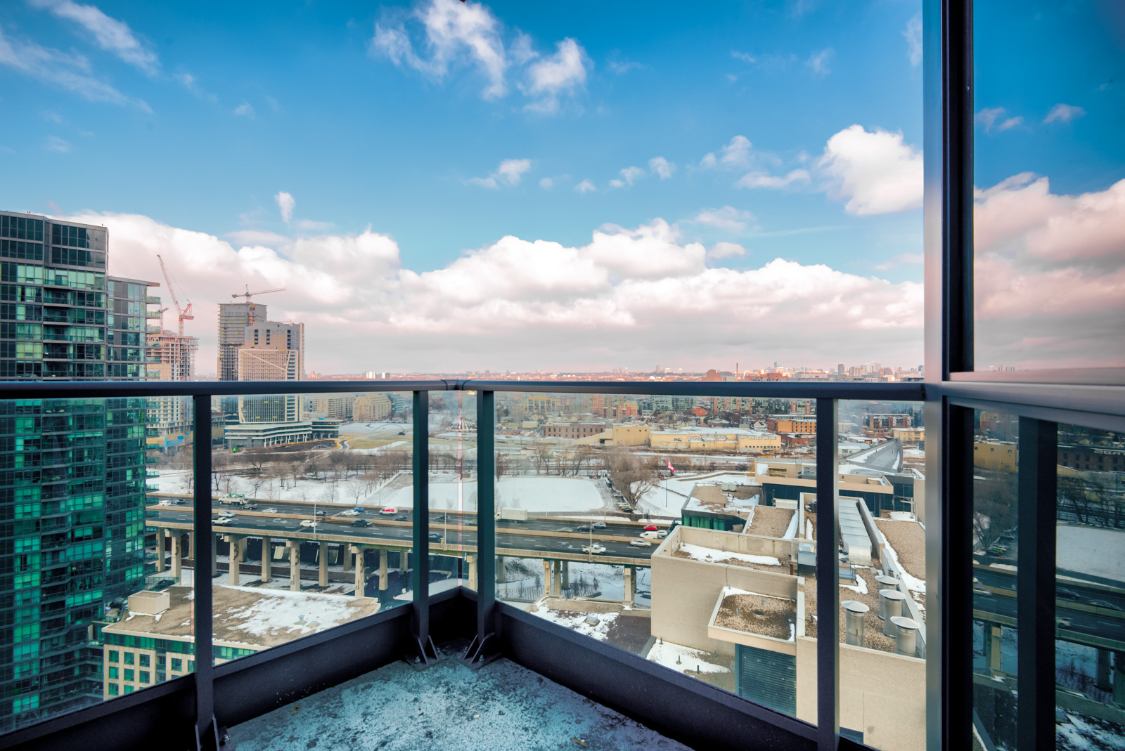 Balcony with black rails and clear glass panels showing Fort York,Toronto.