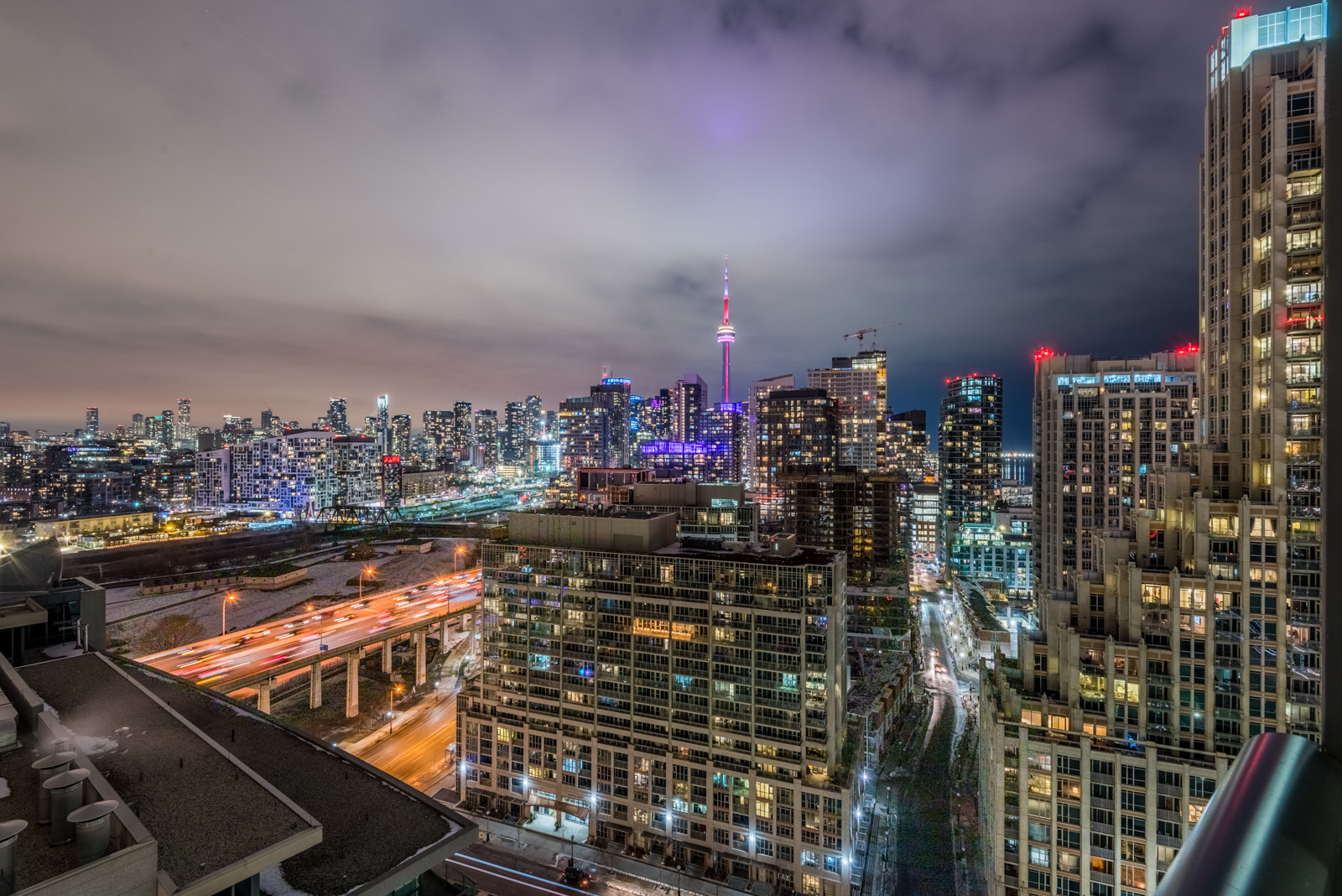 Night view of CN Tower, Downtown Toronto and Gardiner Expressway with colourful lights.