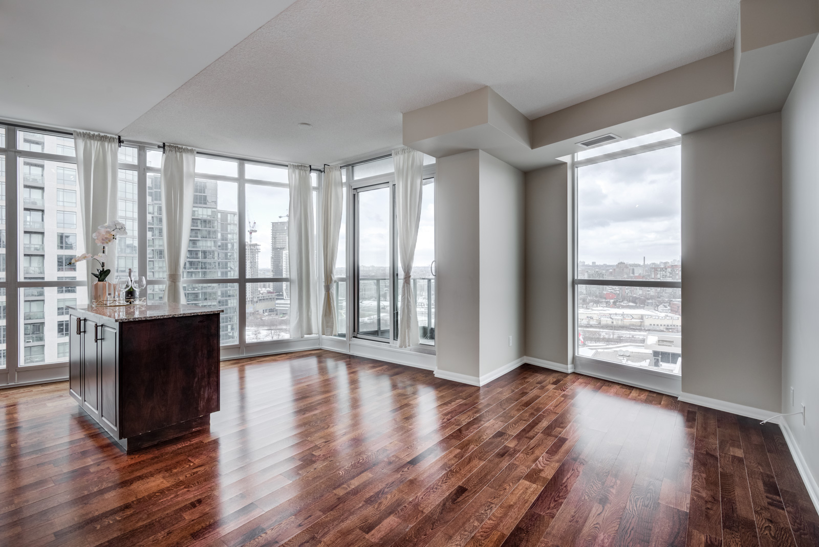 Empty condo unit of 215 Fort York Blvd with kitchen island, dark hardwood floors and several large windows.
