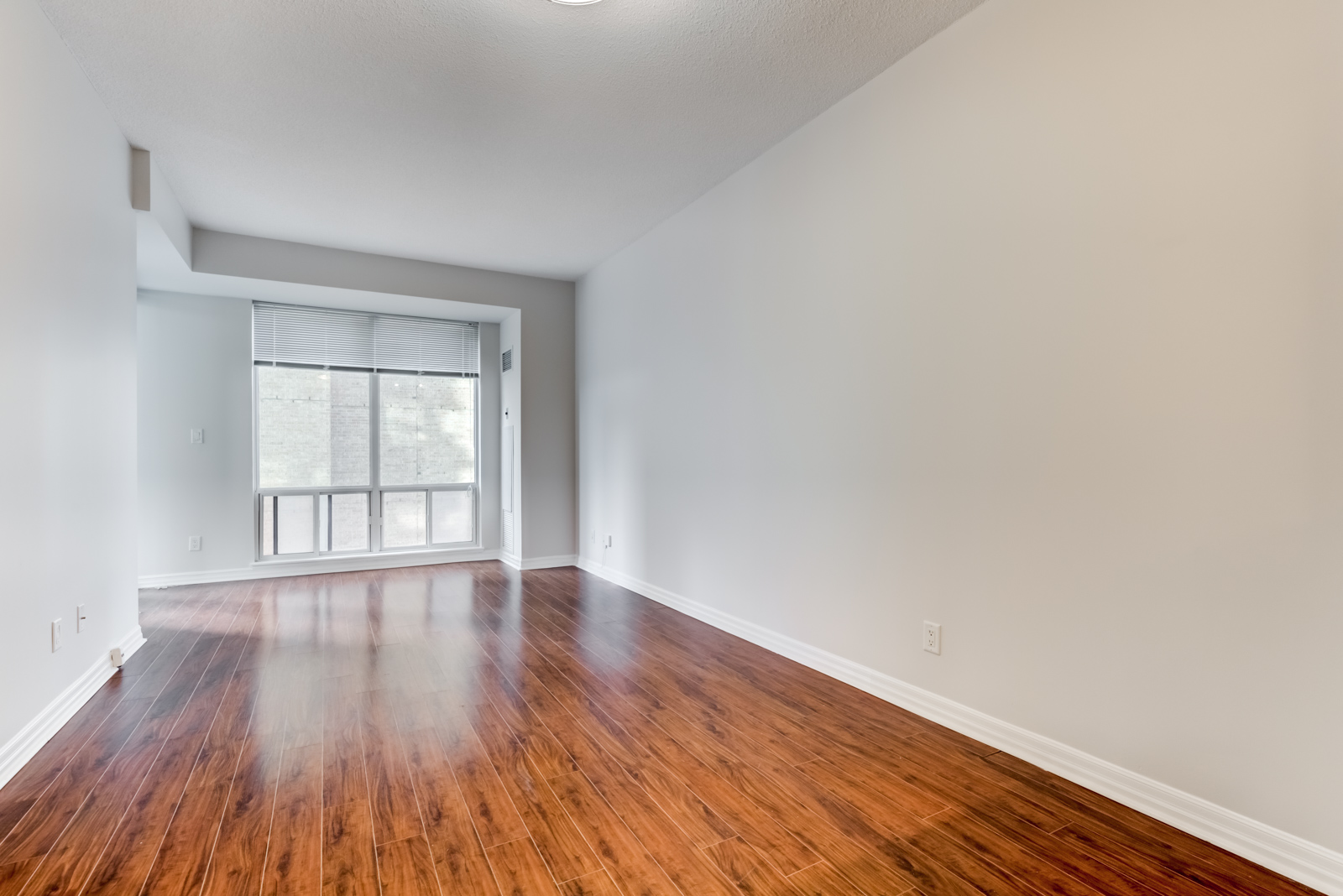 Empty living and dining room of 300 Bloor St E Unit 1809 with dark brown laminate floors shining with light from window.
