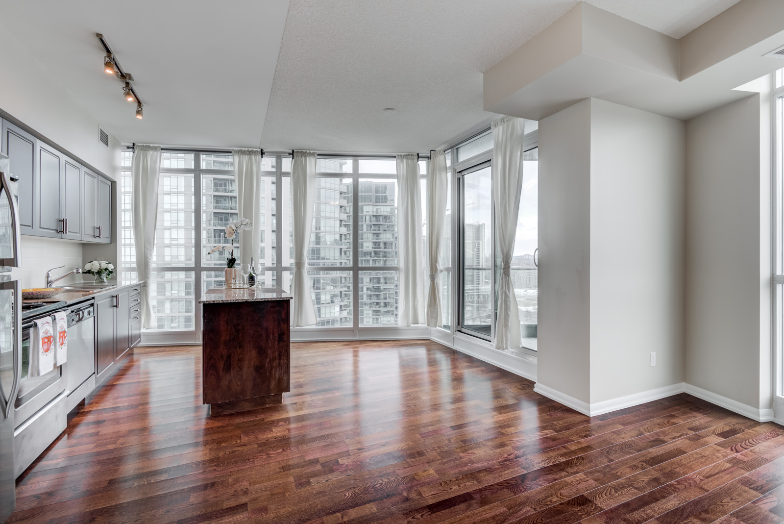 Gray walls and shiny dark brown hardwood floors of 215 Fort York Blvd.