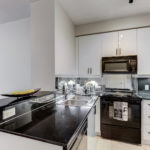 Renovated kitchen with black counters, stove and fridge and white cabinets at 300 Bloor St E Unit 1809.