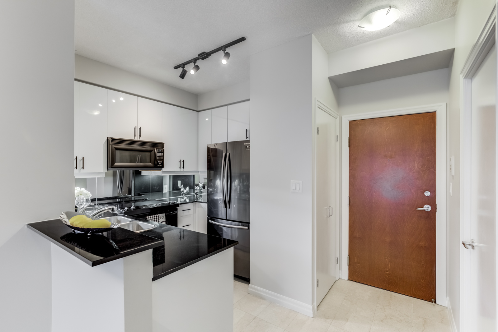 Renovated kitchen of 300 Bloor St E Unit 1809 with centre island, black counter tops and white sides.