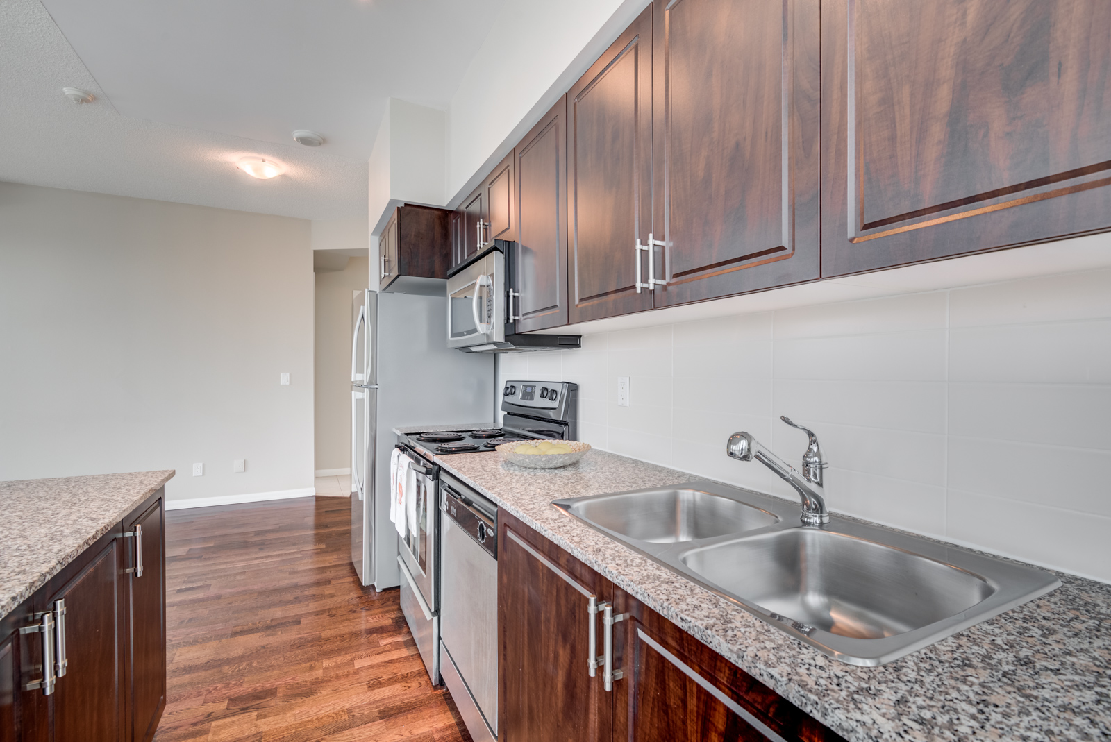 Close up of 215 Fort York Blvd kitchen with speckled granite counters and dark wood cabinets.