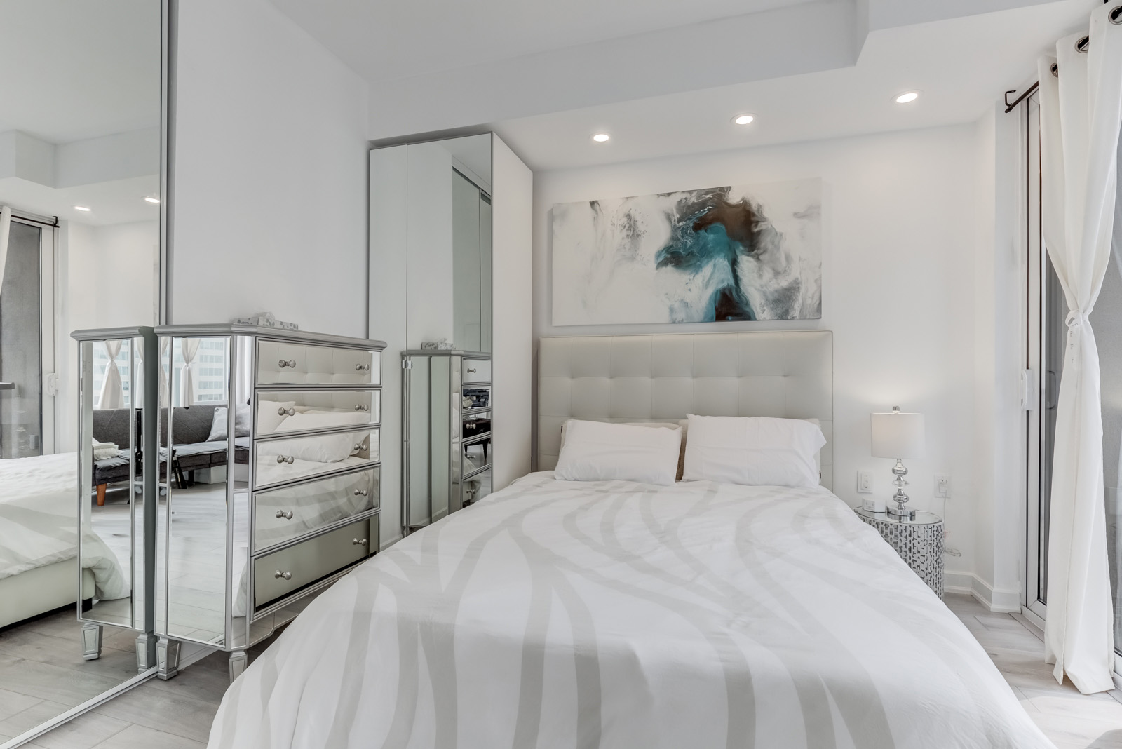85 Bloor Unit 1814 chic master bedroom with silver armoire, tall closet with mirror doors and potlights.