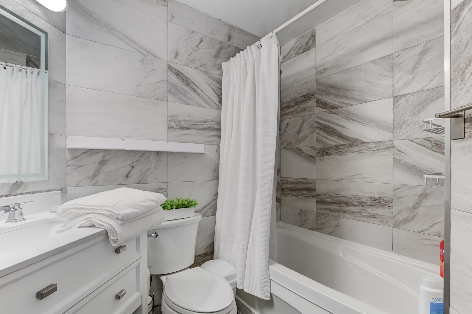 Gorgeous 4-piece bathroom white and gray rectangular tiles, white shelves and sink with drawers.