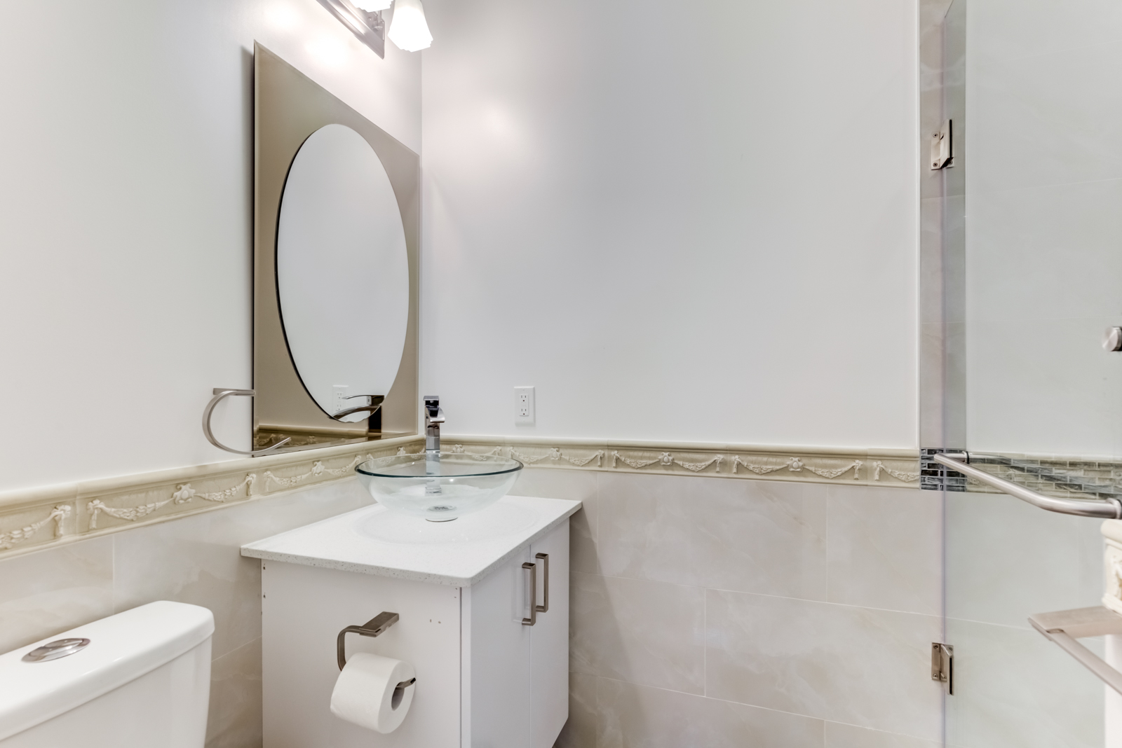 Renovated bathroom at 120 McGill St with white vanity, oval mirror and walk-in shower.