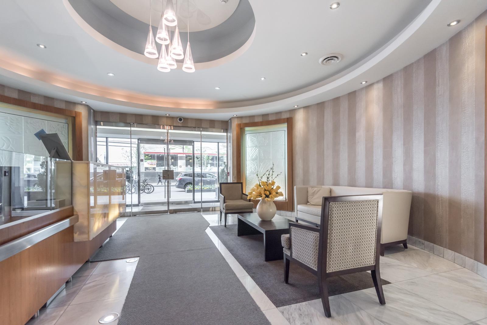 Elegant lobby and concierge desk of 85 Bloor Condos in Toronto.