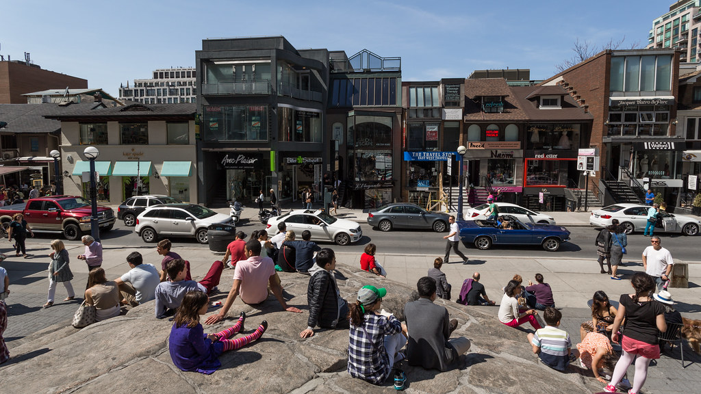 Crowd sitting on ancient rock at Village of Yorkville Park in Toronto.