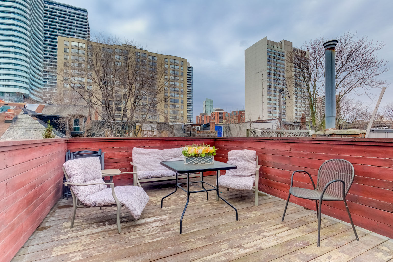 Outdoor wooden deck with chairs and tables on third floor of 120 McGill St.