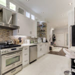 Gorgeous renovated kitchen with modern appliances, shiny white cabinets and tiled backsplash.