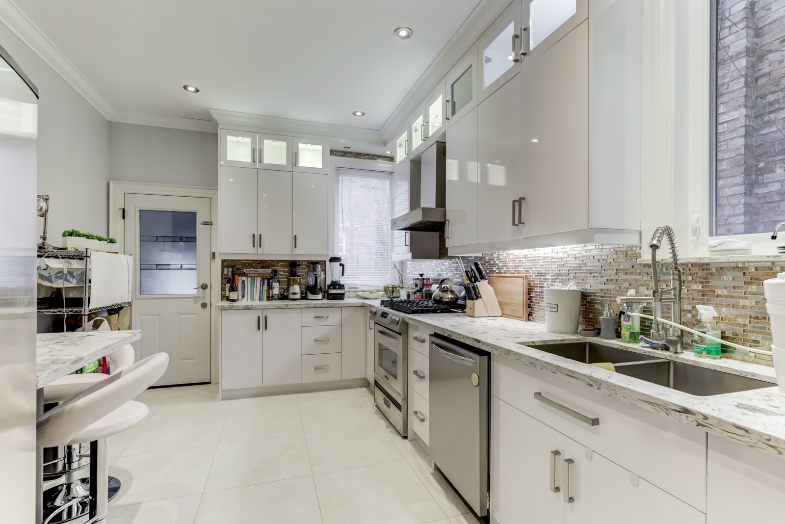 120 McGill St, renovated kitchen with silver appliances, pot-lights and gleaming white cabinets.