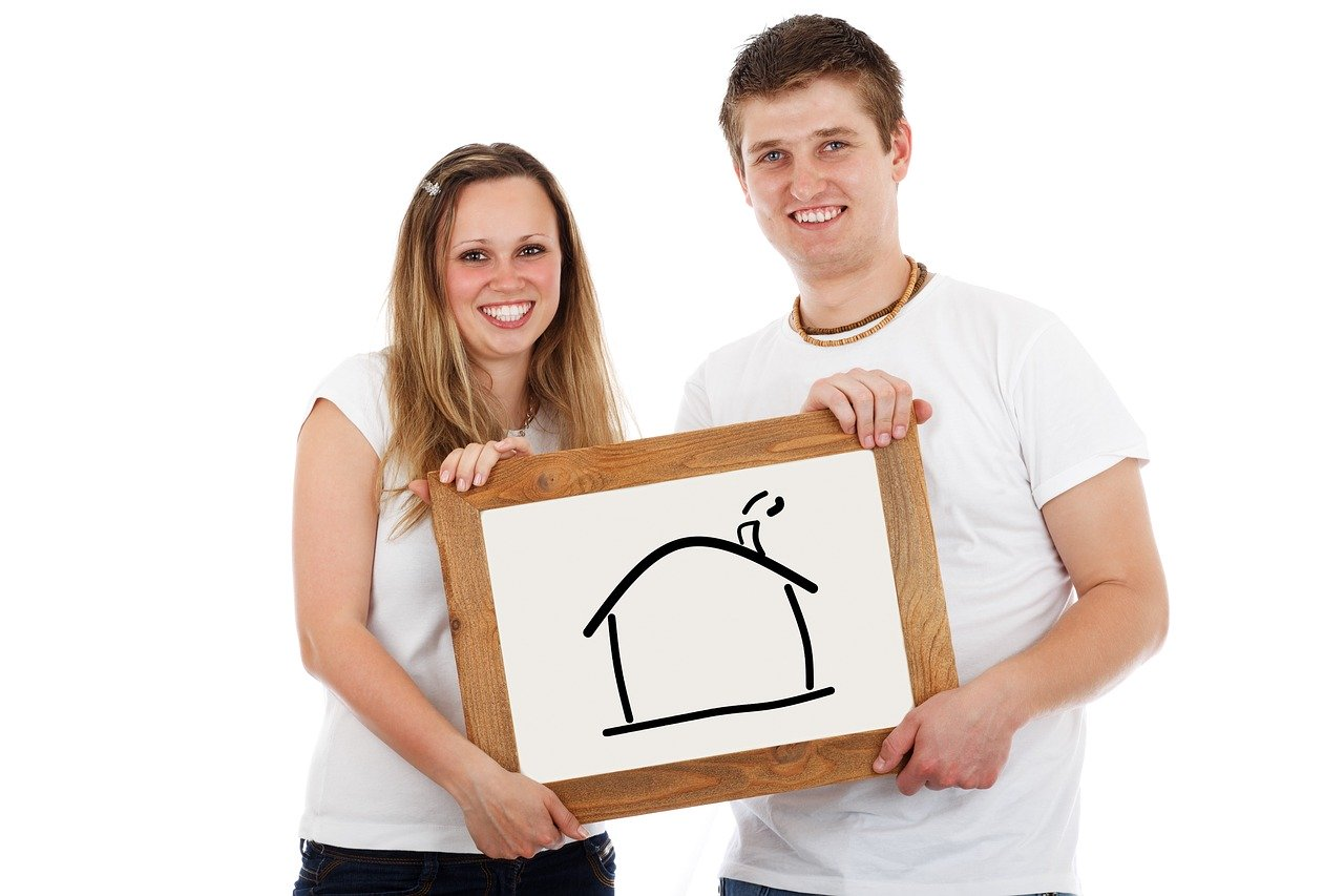 Young couple holding white board with drawing of house.