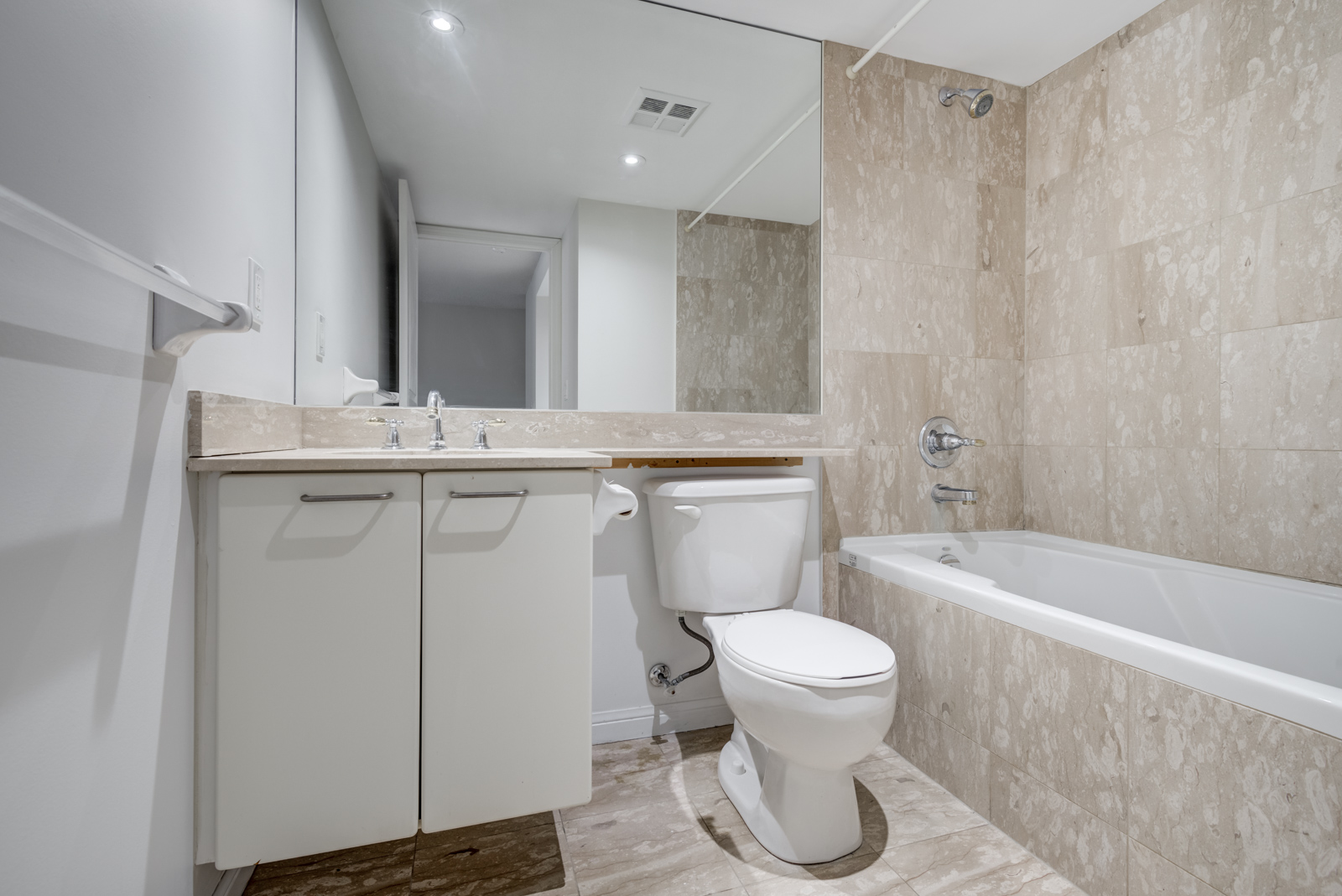 4-piece bathroom with beige tiles, tub, sink and large mirror.