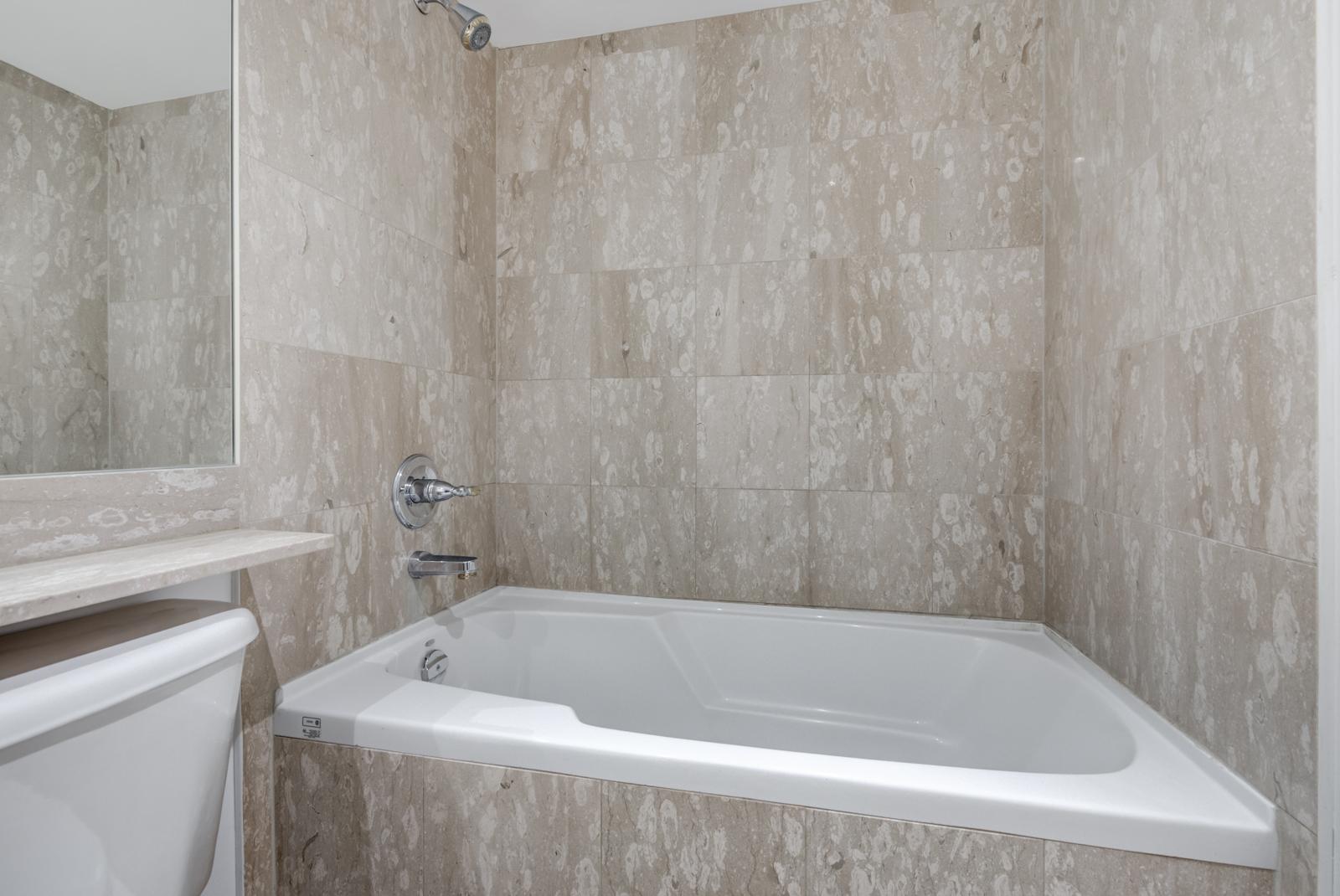 Closeup of 140 Simcoe St E Unit 921 soaker tub with tiles and white trim.