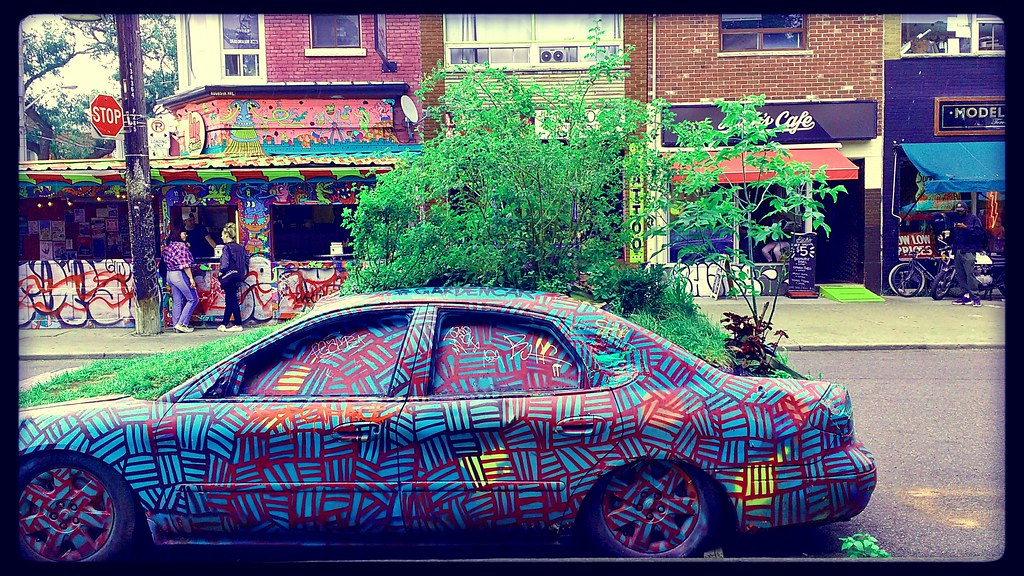 A graffiti-painted car and colourful shops in Toronto's Kensington Market.