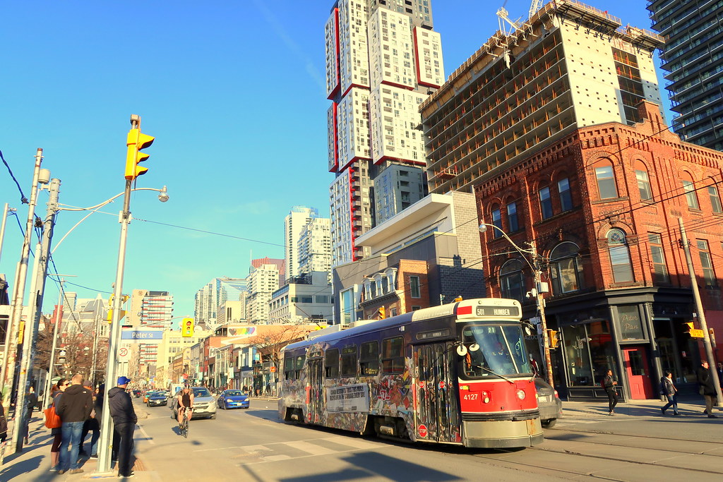 Pedestrians, cyclists, cars and red TTC streetcar on Queen St in Toronto's Entertainment District.