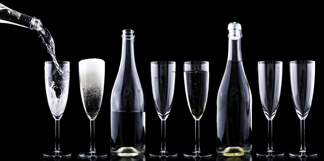 Bottle pouring champagne into neatly arranged glasses.