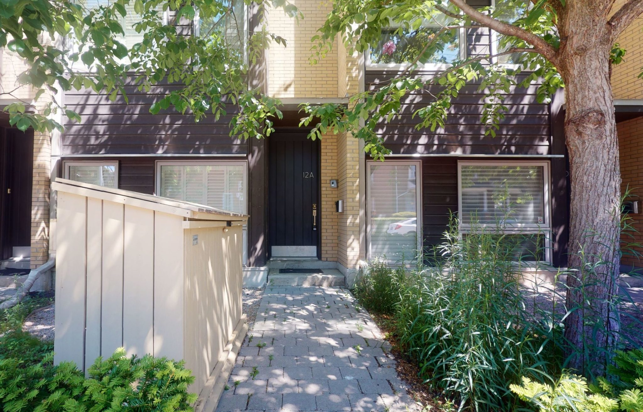 Front entrance of 12A Cecil St, a dark-brick 3-storey condo townhouse.