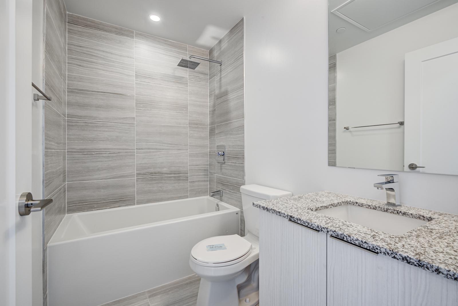 120 Parliament St Unit 1610 bathroom with dark tiles, gray walls and soaker tub.