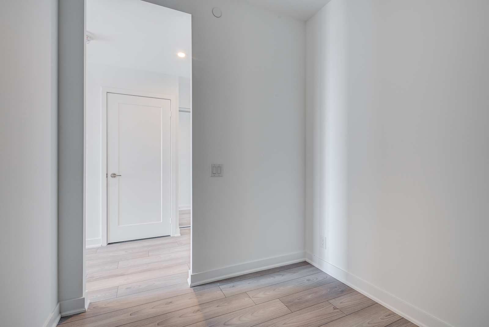 Empty condo den with laminate floors and gray walls.