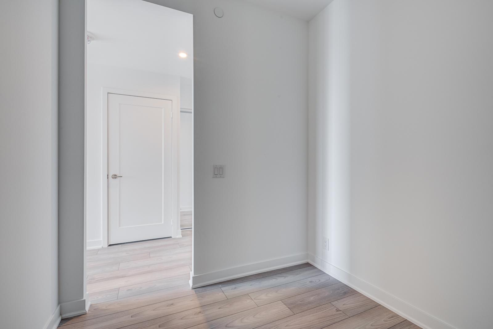 Empty condo den with laminate floors and gray walls.