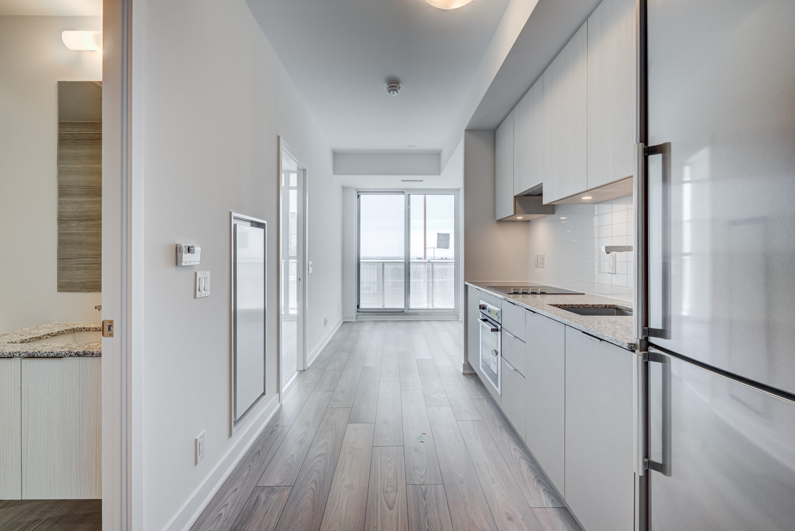 Condo with laminate floors and light gray walls.