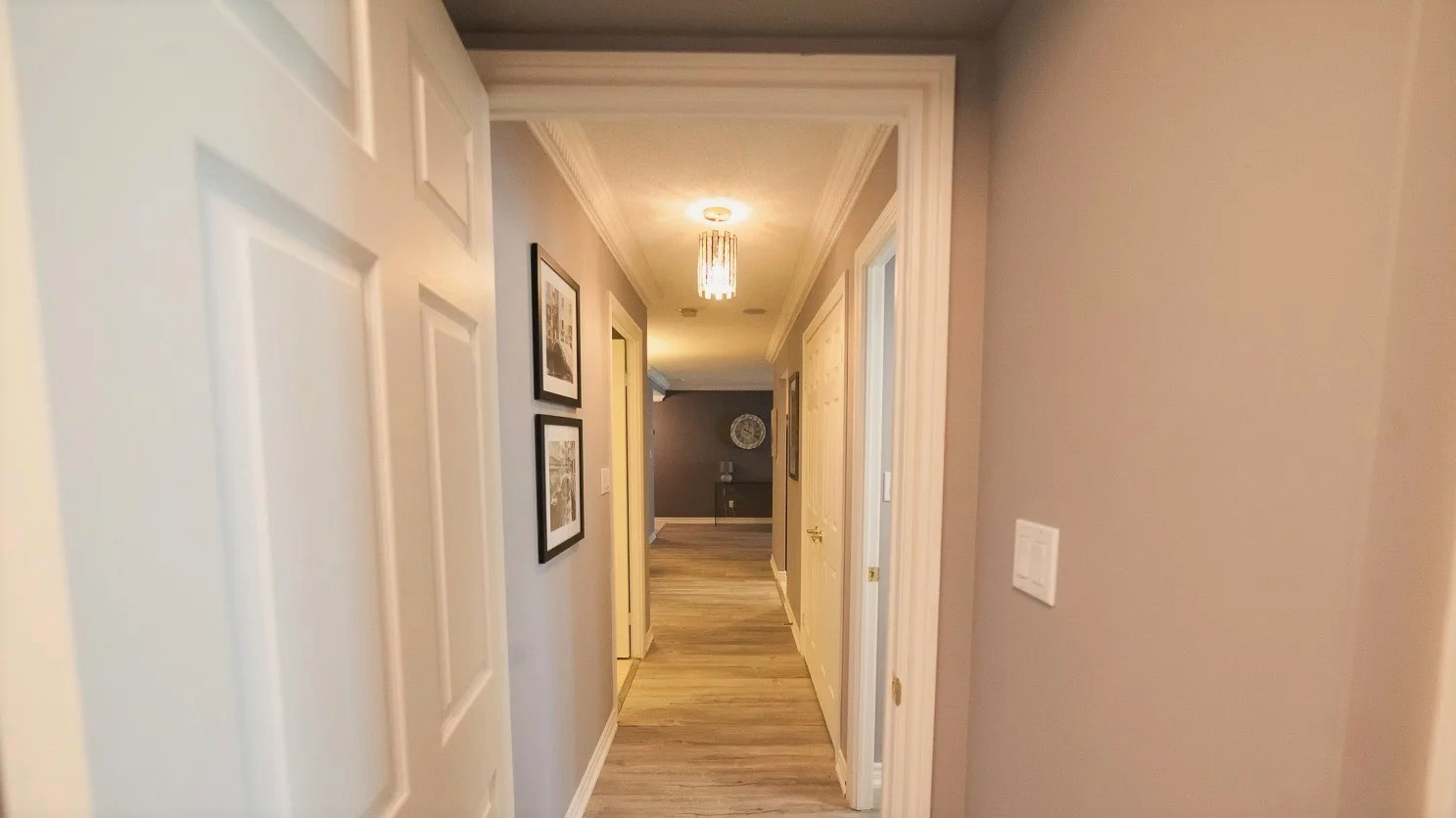 168 Simcoe foyer with new laminate floors and framed photos on walls.