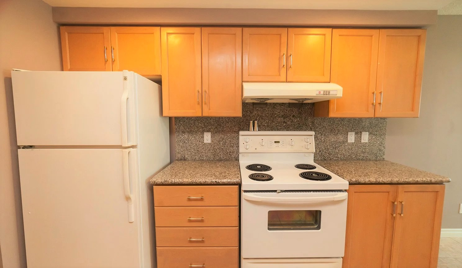 68 Simcoe kitchen with white fridge and stove, wooden cabinets and granite counters.