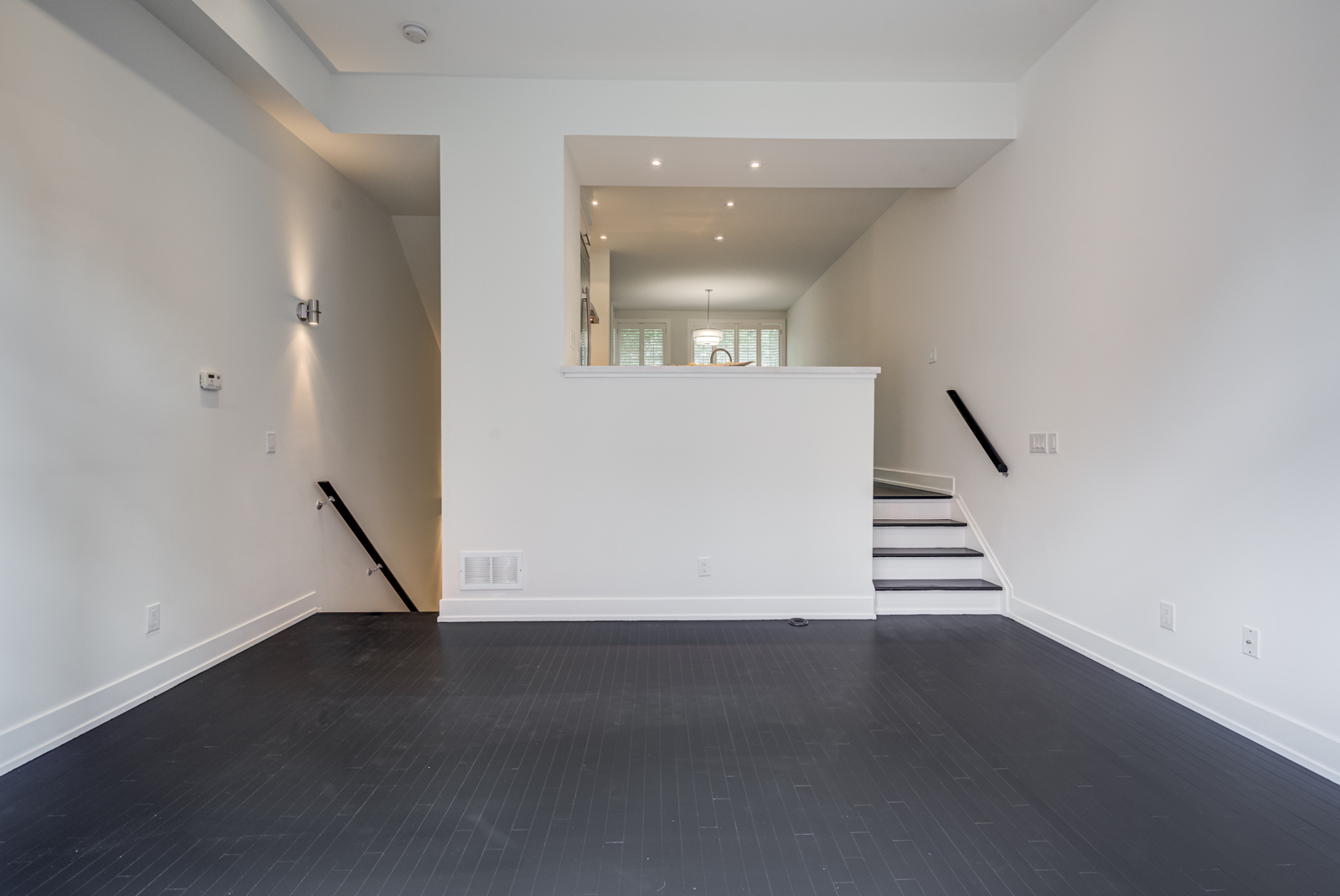 Empty condo with black hardwood floors.